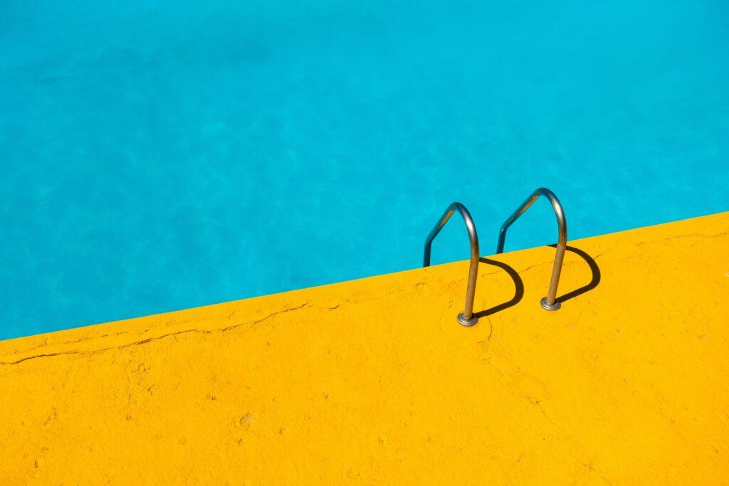 piscina con sfondo giallo sole protezione solare