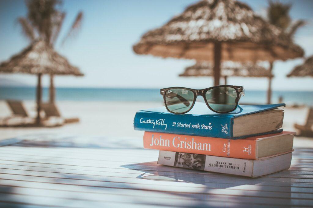 spiaggia sullo sfondo, libri e occhiali da sole in primo piano, protezione solare