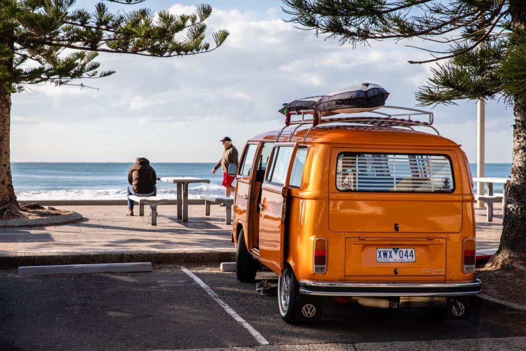 spiaggia sullo sfondo e persone che osservano il mare, in primo piano un camioncino volkswagen arancione protezione solare