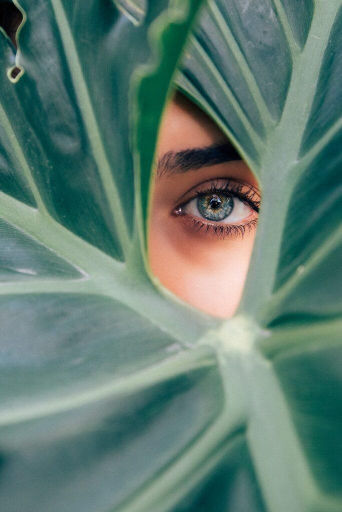 occhio verde di donna su sfondo di foglia verde di banano